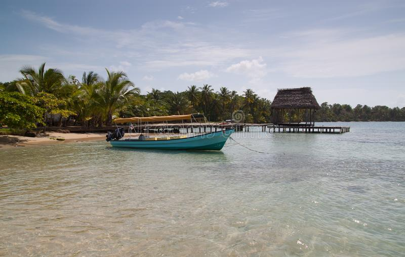 Playa tropical con el barco y el muelle imagen de archivo