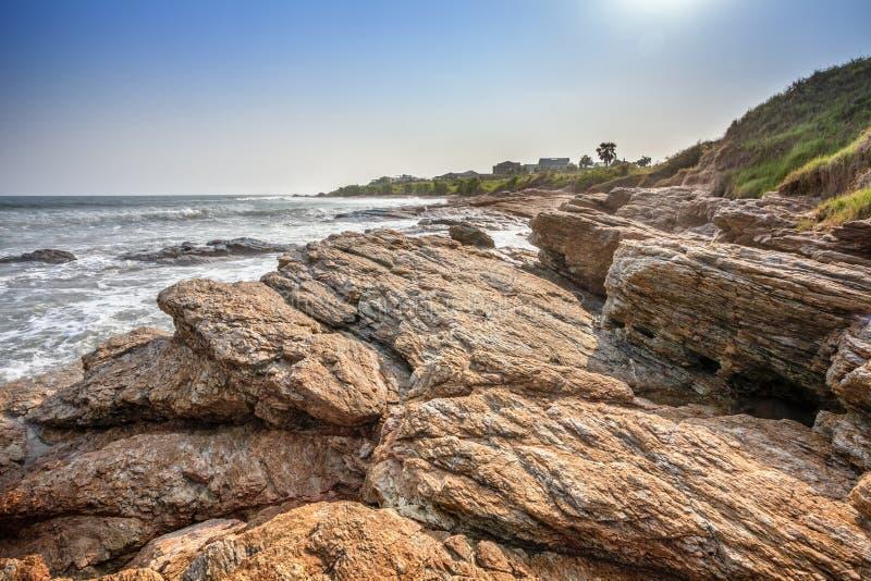 Playa tropical con las ondas que se estrellan en rocas en las Áfricas occidentales fotografía de archivo libre de regalías