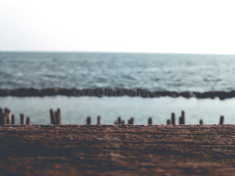 Playa tropical de la falta de definición con la onda de luz del sol del bokeh en el fondo de madera del extracto de la tabla de l imagen de archivo libre de regalías