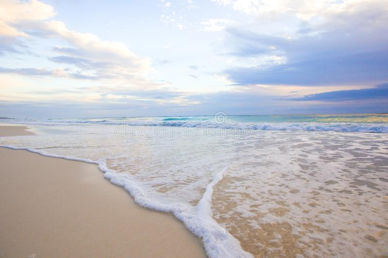 Playa tropical idílica con la arena blanca, agua del océano de la turquesa y el cielo colorido hermoso en la isla caribeña imagenes de archivo