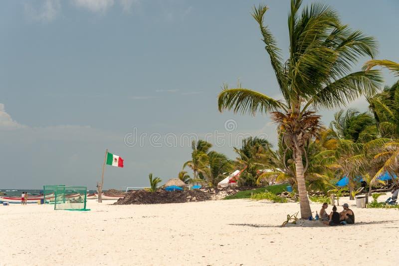 Playa Tulum strand med palmträd och den mexikanska flaggan arkivfoto