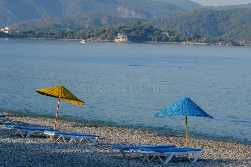 Playa vacía con dos paraguas y camas del sol Barco en el horizonte foto de archivo