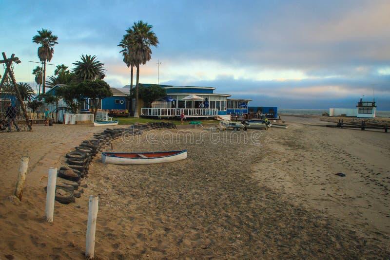Playa vacía de la costa atlántica con el barco, las palmeras y los restaurantes en la puesta del sol foto de archivo