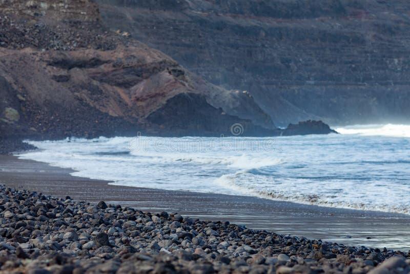 Playa volcánica negra y paisaje del océano foto de archivo