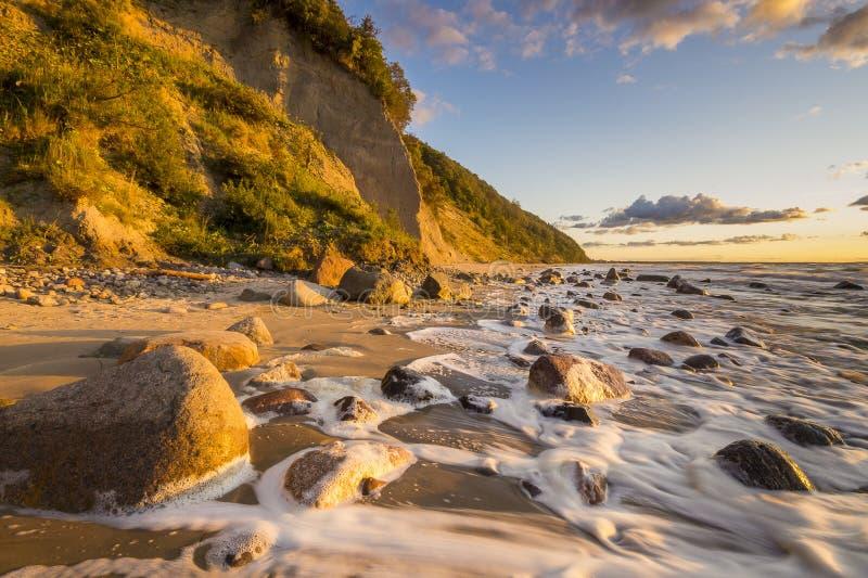 Playa y acantilado teniendo en cuenta la puesta del sol maravillosa foto de archivo
