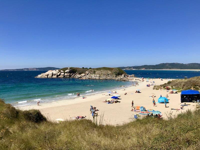 Playa y algunas rocas durante un día de verano hermoso y soleado en Sanxenxo Galicia España imágenes de archivo libres de regalías