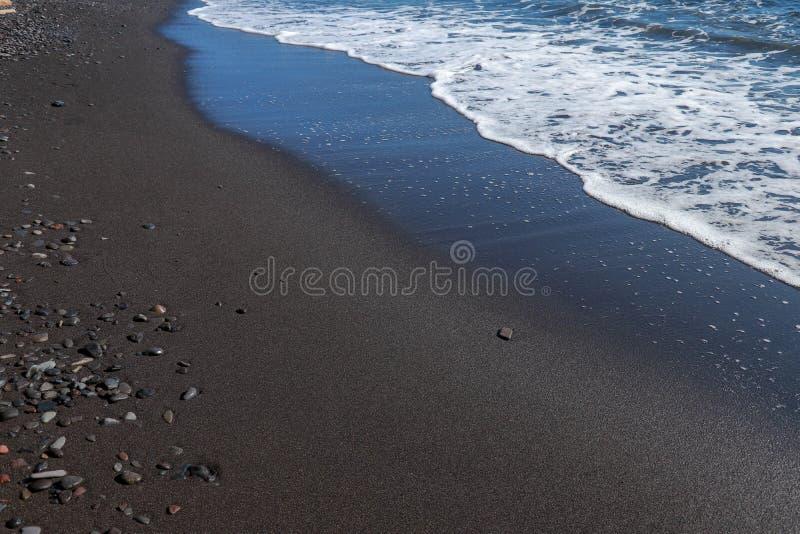 Playa y guijarros volcánicos finos negros de la arena en la isla de Bali en Indonesia La agua de mar alcanza la costa y las vuelt imagen de archivo libre de regalías