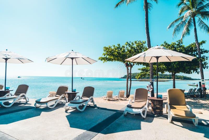 Playa y mar tropicales hermosos con el paraguas y la silla alrededor imágenes de archivo libres de regalías