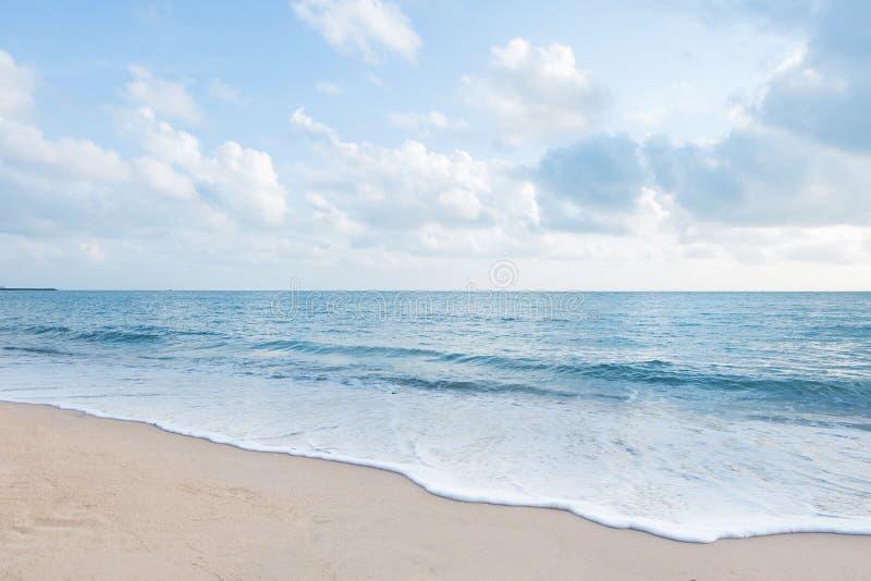 Playa y olas oceánicas blancas hermosas de la arena con el cielo azul claro fotografía de archivo