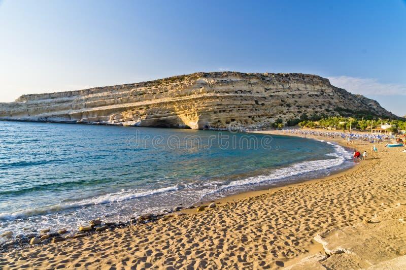 Playa y roca grande con las pequeñas cuevas, isla de Matala de Creta imagenes de archivo