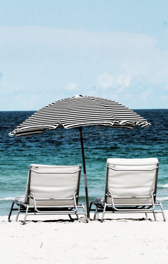 Playa y sillas imagenes de archivo