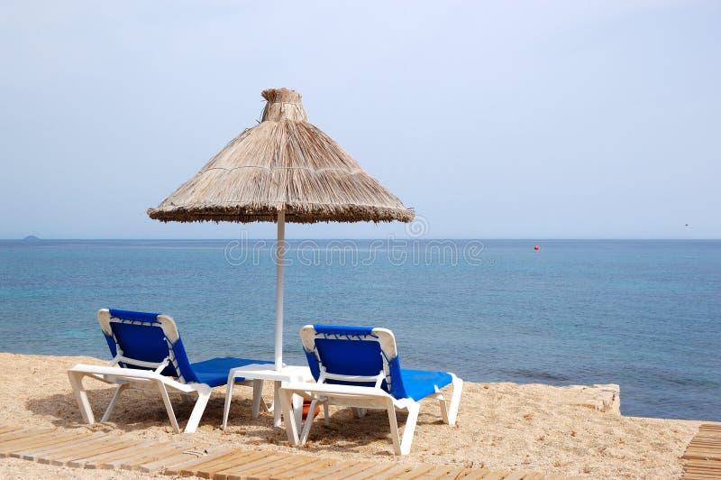 Playa y sunbeds del hotel popular fotografía de archivo