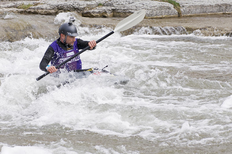 Playboat in River Race - Port Hope, March 31, 2012. A participant paddles his playboat through the Ganaraska River rapids on March 31, 2012 in Port Hope, Ontario royalty free stock photography