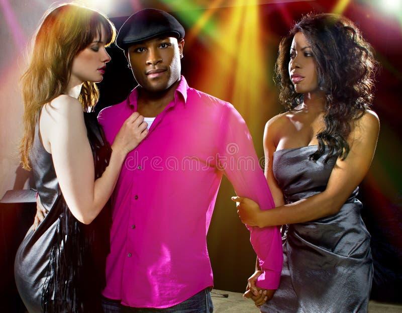 Playboy at Nightclub. Charming single men with two women at a nightclub royalty free stock image