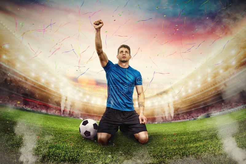 Football player exults in a stadium with audience stock photo
