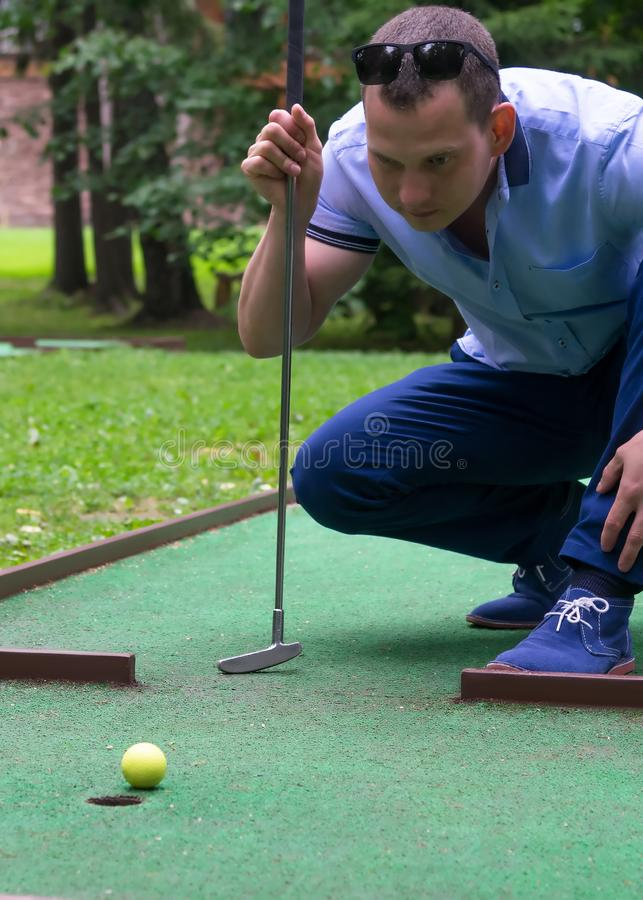 Player looks at his hit on a mini golf course, close-up royalty free stock photos