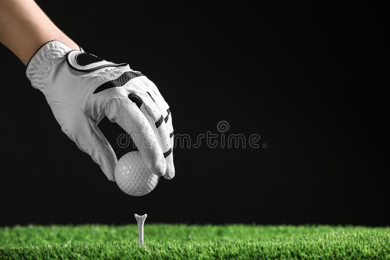 Player putting golf ball on tee against black background. Space for text royalty free stock photography