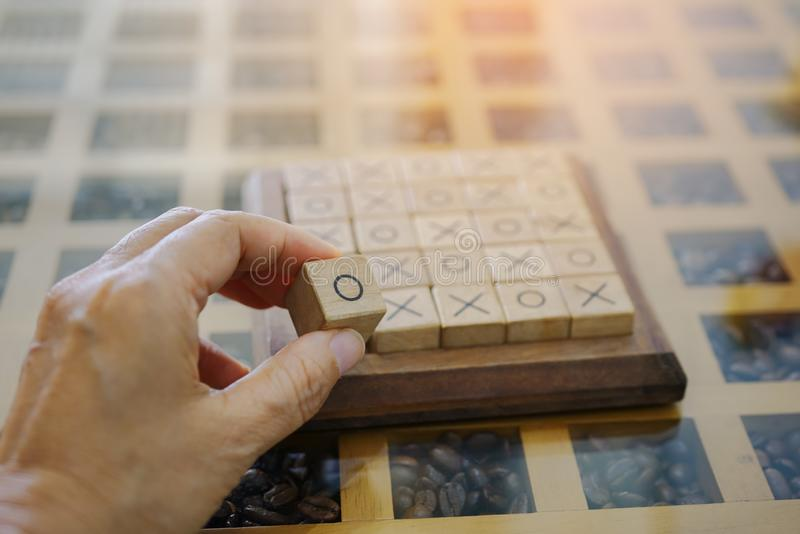 Player`s hand hold an o block  of wooden  xo game royalty free stock photography