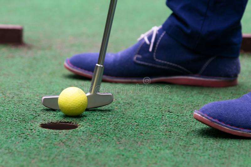 Player`s last shot before the hole in mini-golf, close-up royalty free stock image