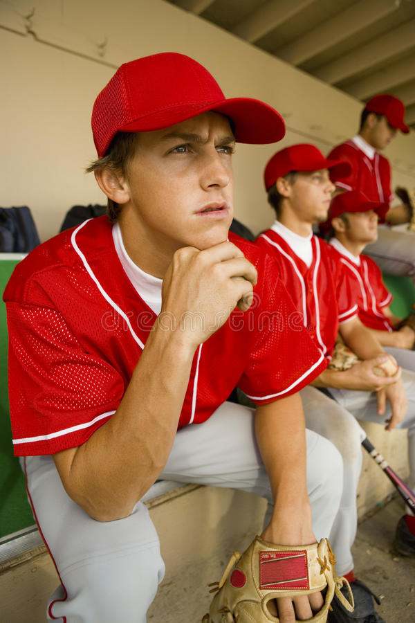 Player Watching The Match Intensely. Baseball player watching the game intensely while sitting in dugout with other players stock image