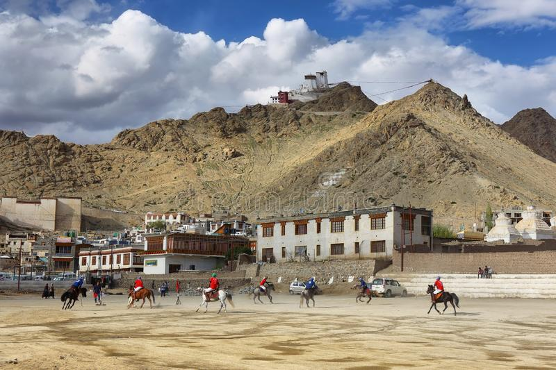 Players in action in Polo Game with Tsemo gompa and Leh palace at background in Leh, Ladakh, India royalty free stock photography
