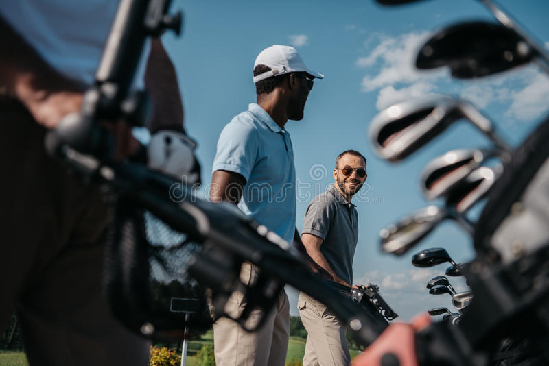 Players going to the golf course, bag with clubs at foreground royalty free stock photos