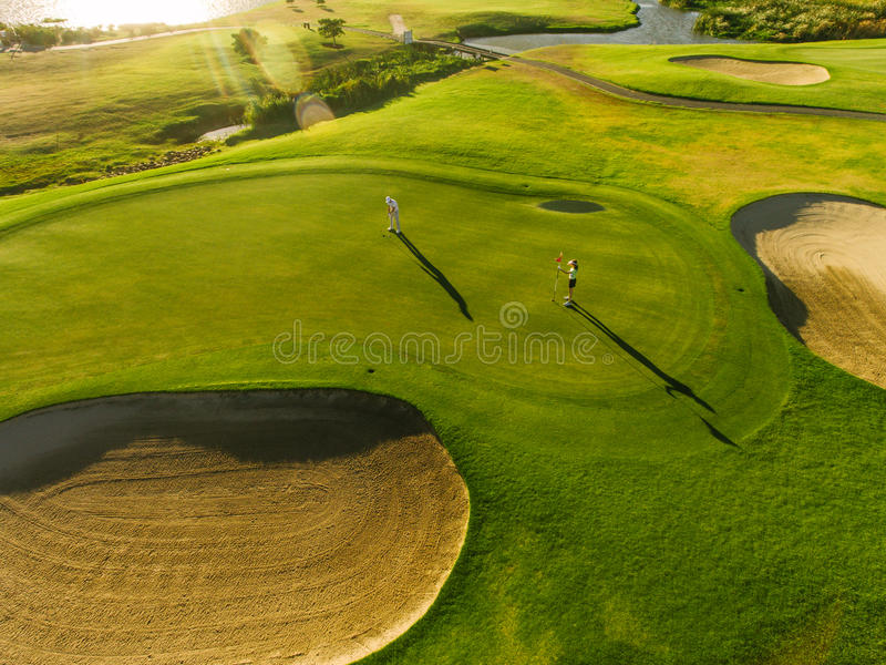 Players on a green golf course stock photography
