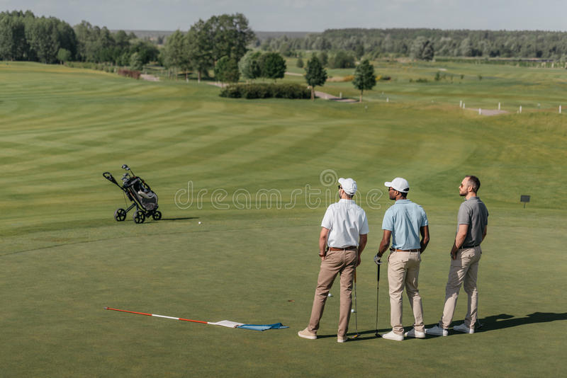 Players looking away while standing on golf pitch royalty free stock photos