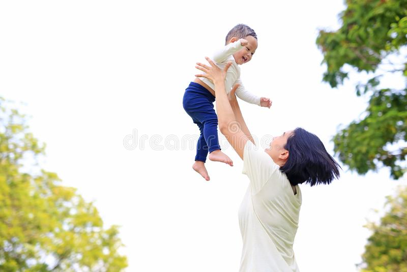 Playful Asian mother throwing up happy baby boy in the nature garden. Mother lifting up son at park royalty free stock images