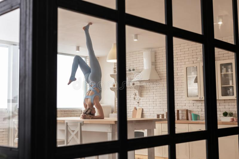 Playful athletic girl standing on her head in kitchen. Magnificent possibilities. Playful athletic girl standing on her head in kitchen while being all alone in royalty free stock images