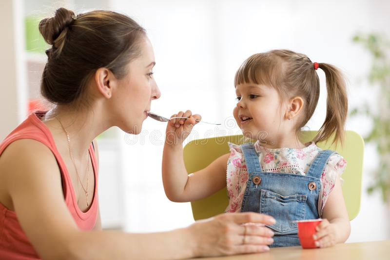 Playful baby girl spoon feeding her mother royalty free stock photography