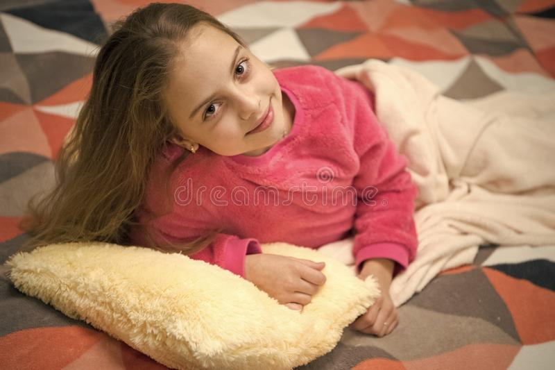 Playful baby relaxing. Pajamas and bedroom textile. Pajamas and clothes for home. Girl little kid wear soft cute pajamas. While relaxing on bed. Comfortable stock photography