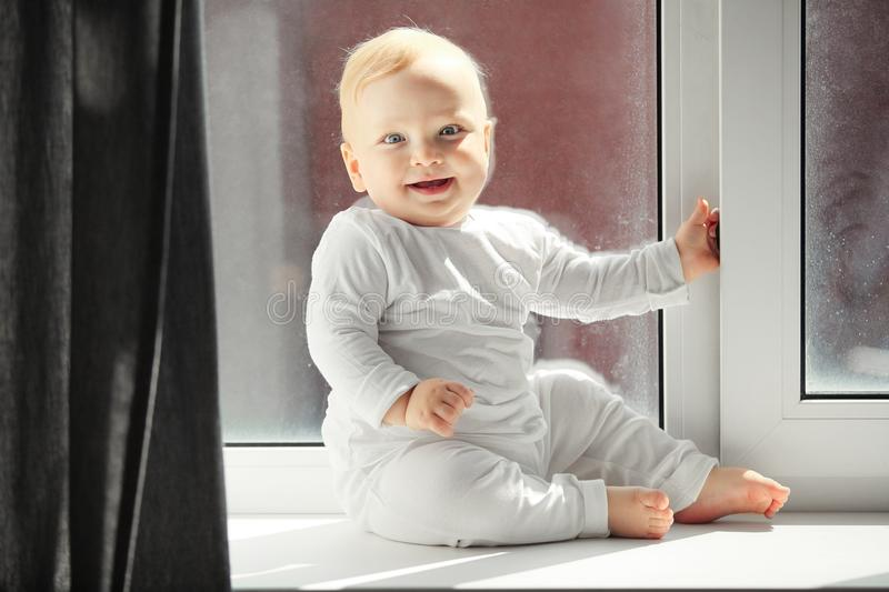 Playful baby sits on windowsill in white overalls. Playful baby with blond hair and grey eyes in white crawlers sits on windowsill full of light that comes from royalty free stock photos