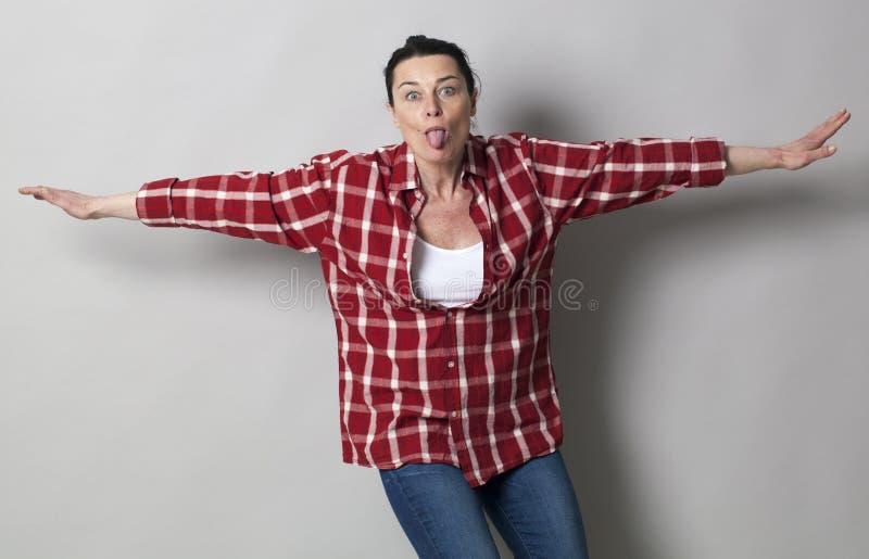 Playful beautiful 40s woman sticking her tongue out. Funny face concept - playful beautiful 40s woman sticking her tongue out with arms open like flying, studio stock photo
