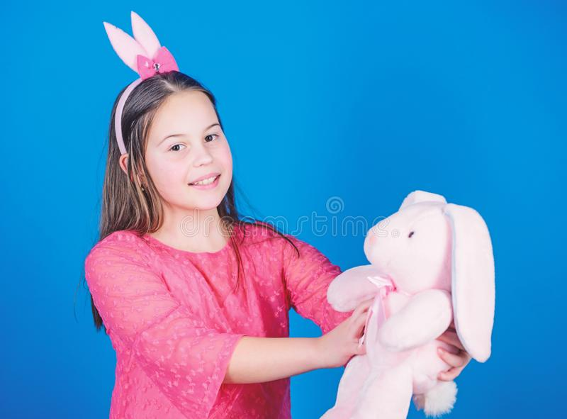 Playful beauty. Little girl with hare toy. Egg hunt. Family holiday. Happy easter. Spring party. Child in rabbit bunny stock photo