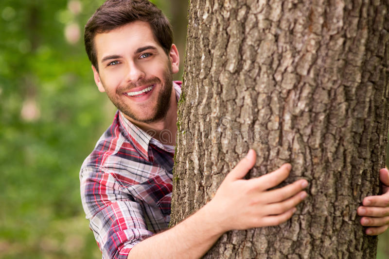 Playful beauty in nature. Handsome young woman looking out of the tree and smiling royalty free stock images