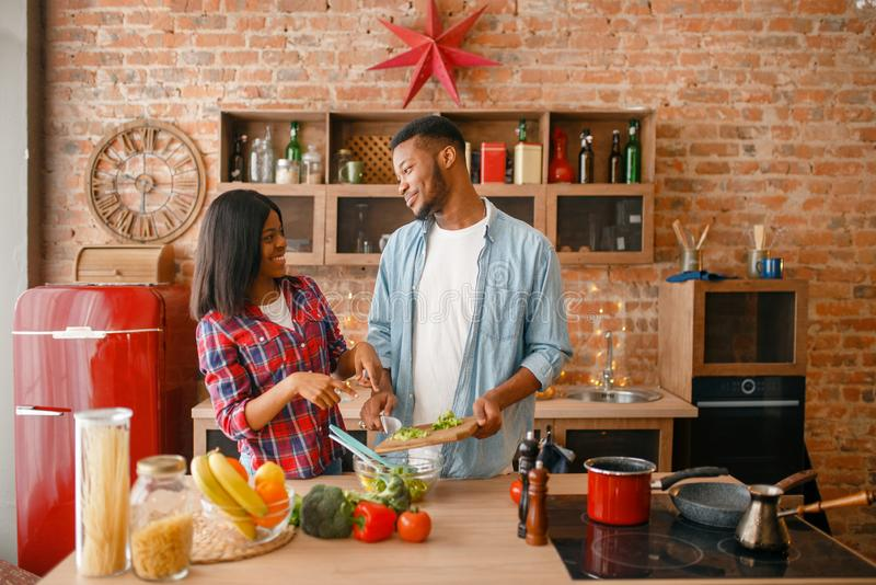 Playful black couple cooking dinner on the kitchen. Playful black couple cooking romantic dinner on the kitchen. African family preparing vegetable salad at home stock photos