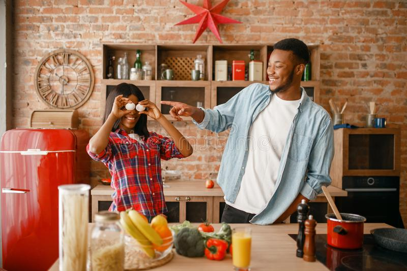 Playful black couple cooking dinner on the kitchen. Playful black couple cooking romantic dinner on the kitchen. African family preparing vegetable salad at home royalty free stock images