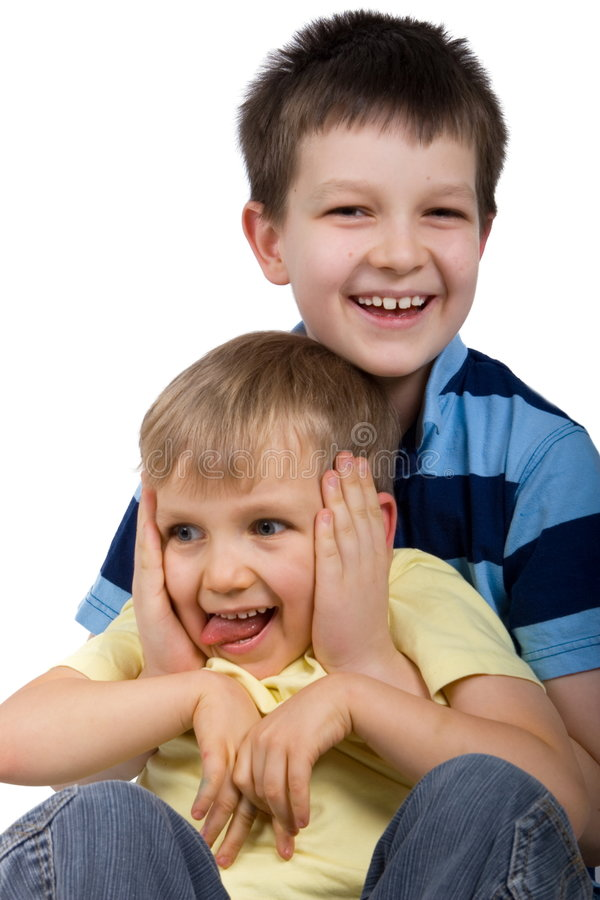 Playful Brothers. Two smiling young brothers in a playful portrait. Isolated on white. Taken in studio royalty free stock photos