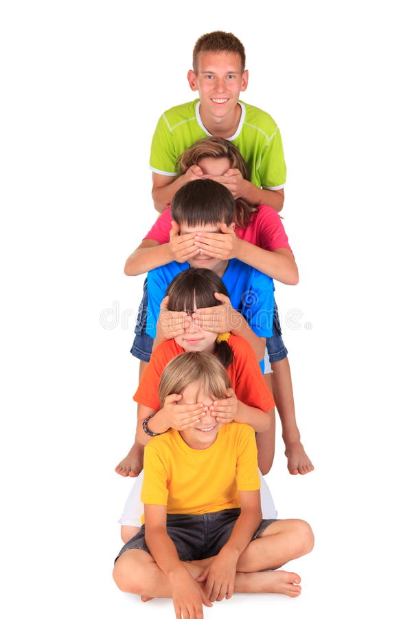Playful brothers and sisters. Three playful brothers and two sisters in a line with the one behind covering the eyes of the one in front royalty free stock images