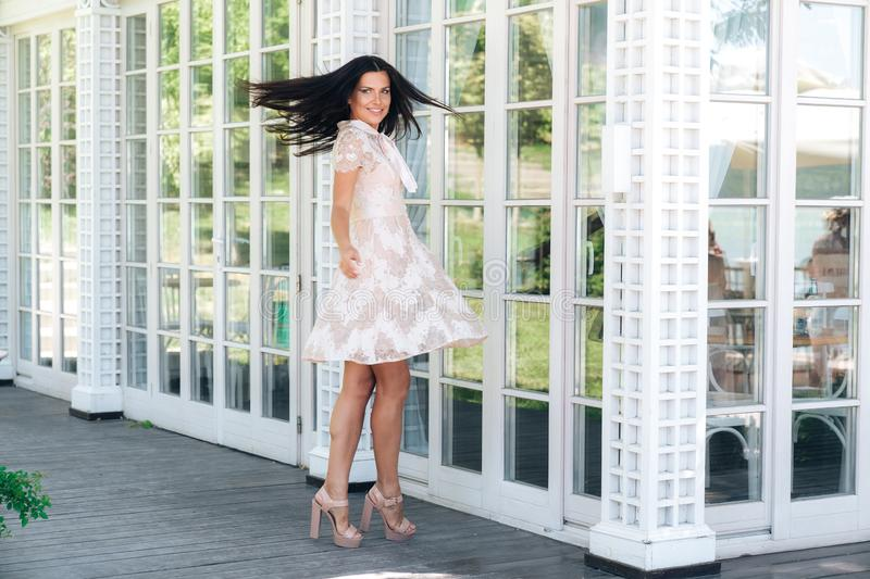 Playful brunette with beautiful long legs posing in beige colour dress outside near a wooden and glass wall royalty free stock images
