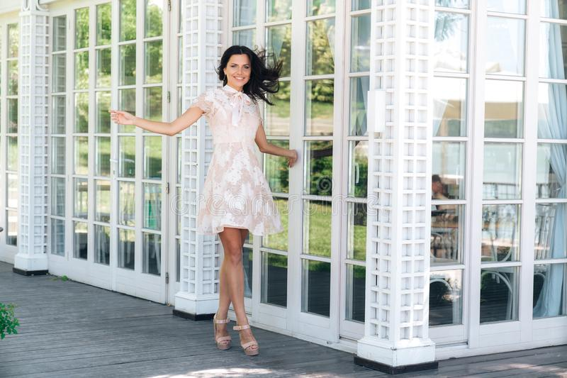 Playful brunette with beautiful long legs posing in beige colour dress outside near a wooden and glass wall royalty free stock photography