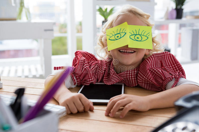 Playful businesswoman with adhesive notes on eyes at office royalty free stock photo