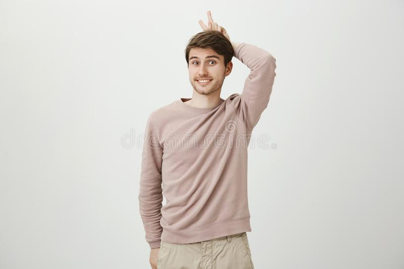 Playful charming european student holding victory or peace sign behind head as if it is horns, standing with cute smile. And positive expression over gray stock photography