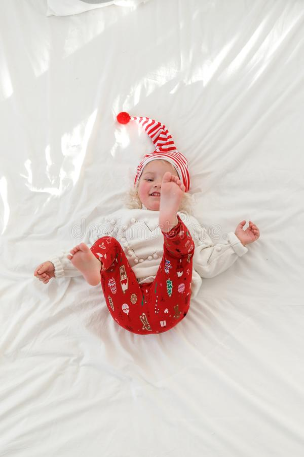 Playful cheerful little girl wears pyjamas and Santa s hat, raises legs, lies on comfortable bed with white bedclothes. Enjoys good morning. Funny adorable royalty free stock image