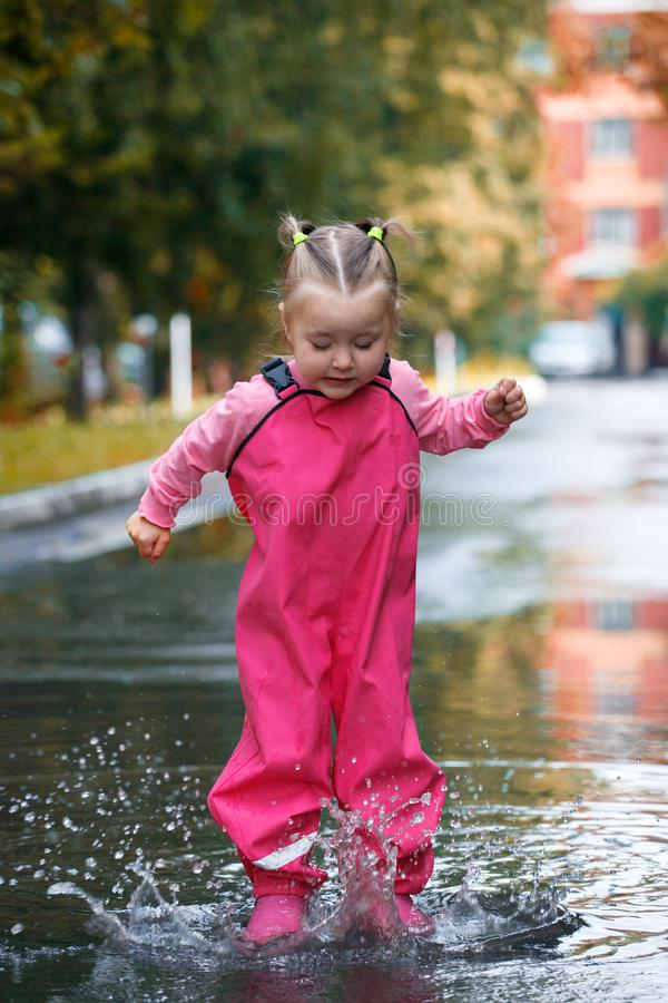 Playful child outdoor jump into puddle in boot after rain on wak, seasonal fun game royalty free stock photo