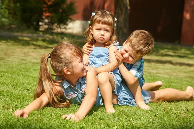 Playful children outdoors in the summer on the grass in a backyard. Happy playful children outdoors in the summer on the grass in a backyard stock photos