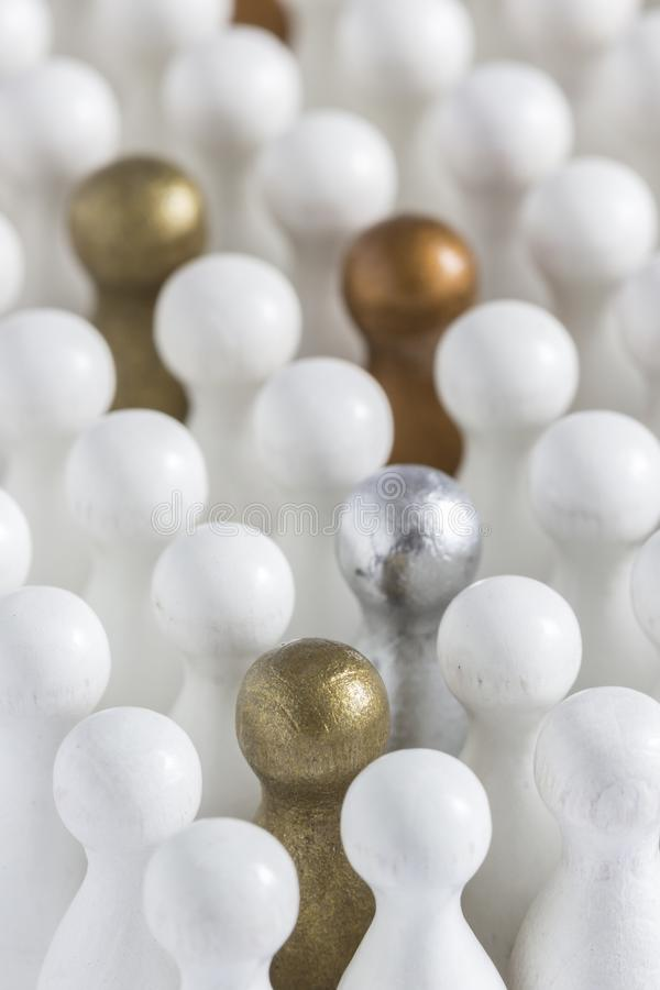Gold, Silver and Bronze game pieces in a crowd of white pieces royalty free stock images