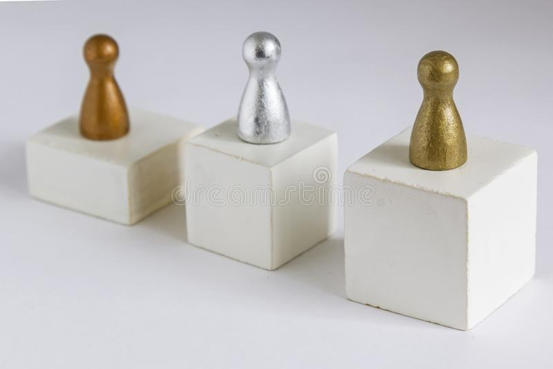 Gold, Silver and Bronze gamefigurine on a winner podium royalty free stock image