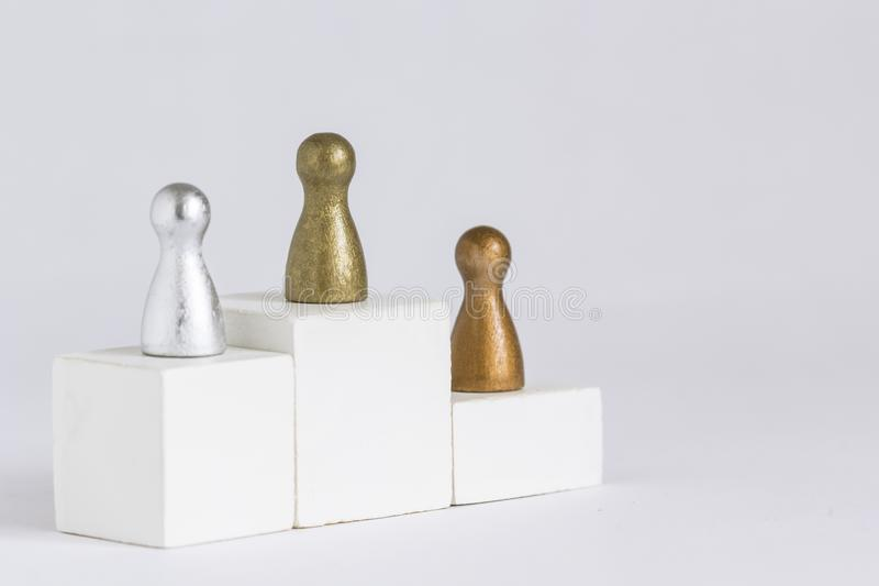 Gold, Silver and Bronze gamefigurine on a winner podium stock image